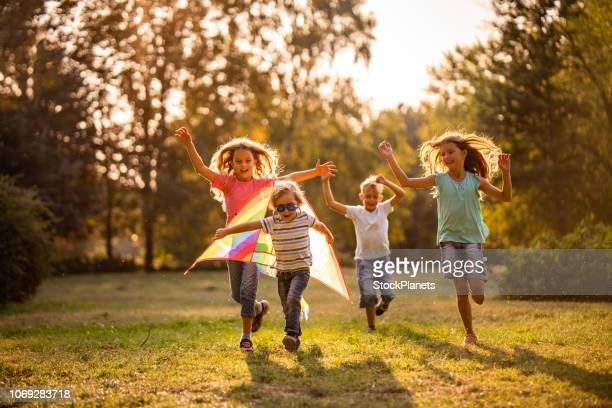 group of happy children running in public park - outdoors stock pictures, royalty-free photos & images