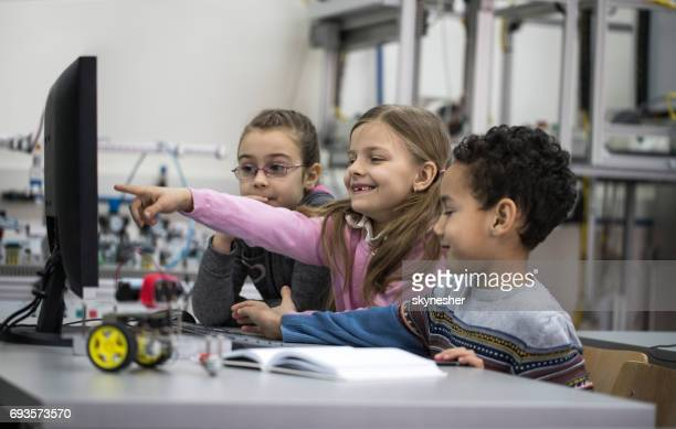 Group of happy children using desktop PC in a laboratory.