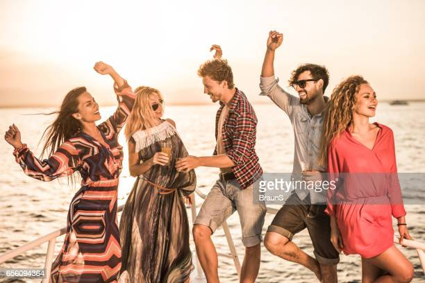 Group of happy friends dancing in summer day at sunset.