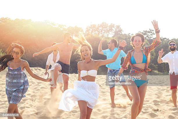 Group of happy friends dancing on the beach
