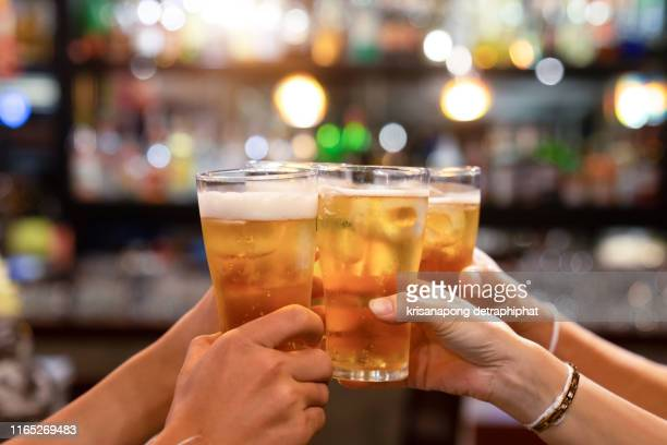 group of happy friends drinking and toasting beer at brewery bar restaurant - friendship concept with young people having fun together at cool vintage pub - focus on middle pint glass - high iso image - honour stock pictures, royalty-free photos & images