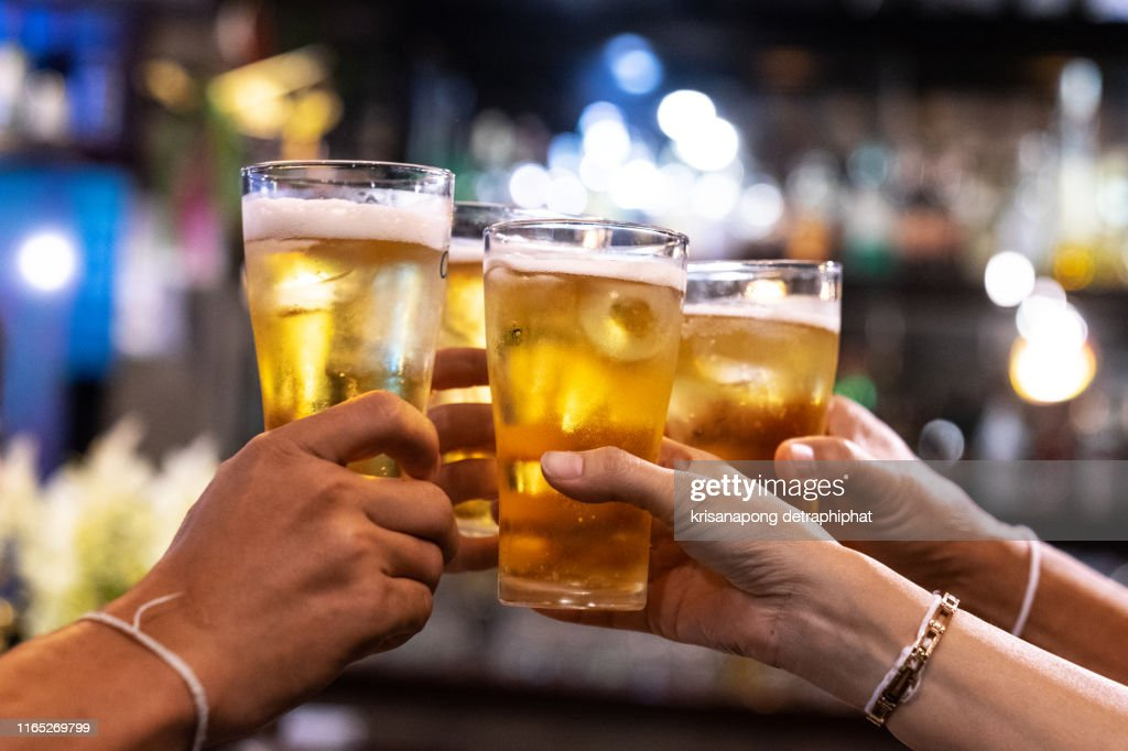 Group of happy friends drinking and toasting beer at brewery bar restaurant - Friendship concept with young people having fun together at cool vintage pub - Focus on middle pint glass - High iso image : Stock Photo