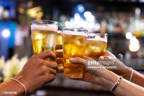 group of happy friends drinking and toasting beer at brewery bar restaurant - friendship concept with young people having fun together at cool vintage pub - focus on middle pint glass - high iso image - pub stock pictures, royalty-free photos & images