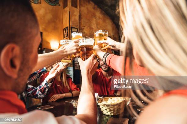 group of happy friends drinking beer at the brewery - pub stock pictures, royalty-free photos & images