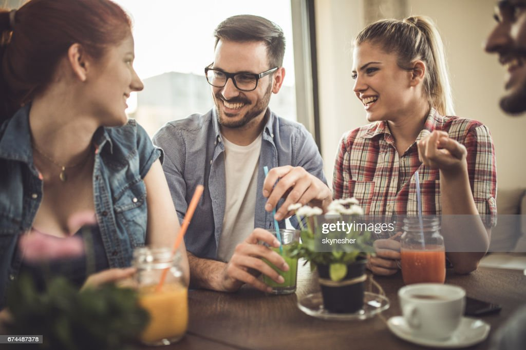 Group of happy friends enjoying in a talk at a cafe. : Stock Photo