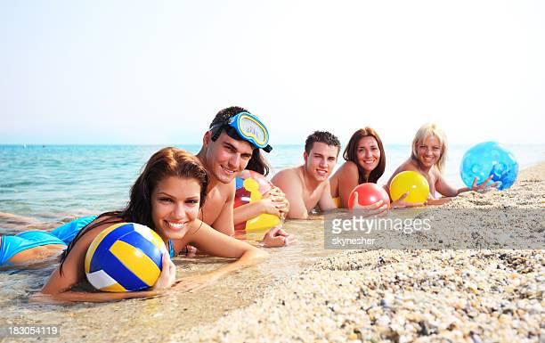 Gruppe von glücklichen Freunde genießen um auf das Meer liegen.