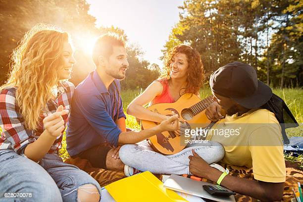 group of happy friends enjoying with music in nature. - tocar - fotografias e filmes do acervo
