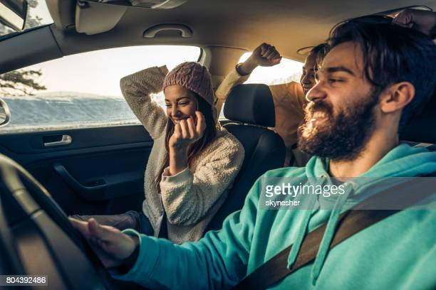 Group of happy friends having fun while dancing during a road trip in the car.