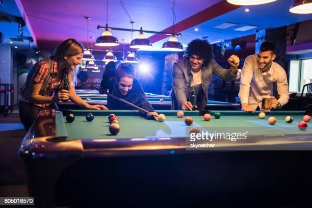 パブでビリヤードをプレイしながら楽しんで幸せな友人のグループです。