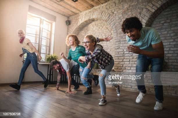 group of happy friends having fun while starting a race at casual office. - starting line stock pictures, royalty-free photos & images