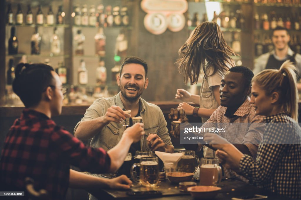 Group of happy friends having fun while toasting with vodka shots in a pub. : Stock Photo