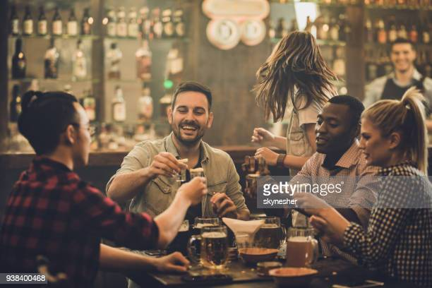 group of happy friends having fun while toasting with vodka shots in a pub. - pub stock pictures, royalty-free photos & images