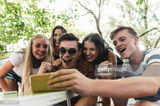 group of happy friends looking at cell phone outdoors - sending stock pictures, royalty-free photos & images