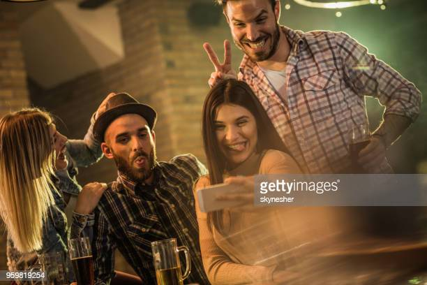 Group of happy friends making faces while taking a selfie in a pub.