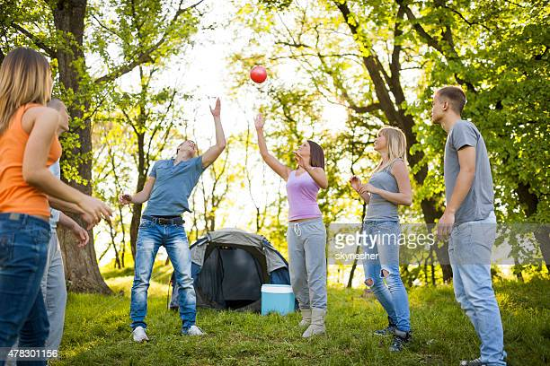 Group of happy friends playing with ball on camping.