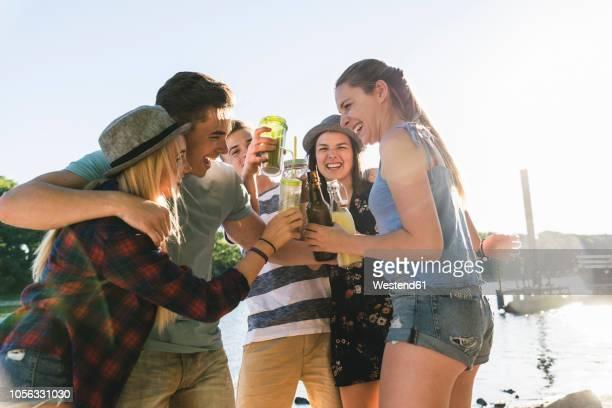 group of happy friends standing at the riverside toasting with drinks - koude dranken stockfoto's en -beelden