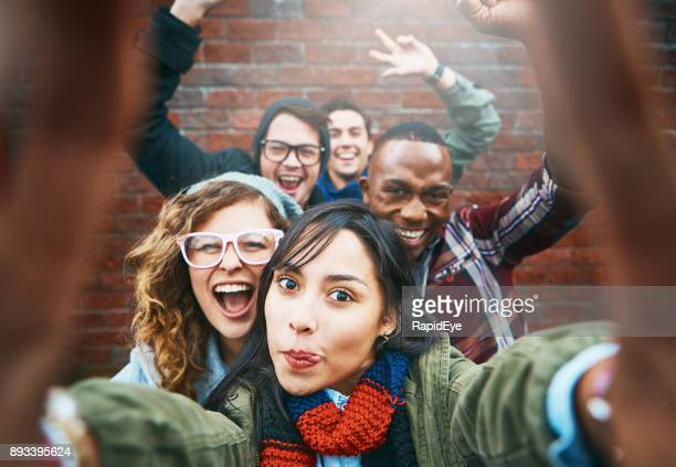 group of happy friends take excited selfie, waving and laughing - arms outstretched stock pictures, royalty-free photos & images