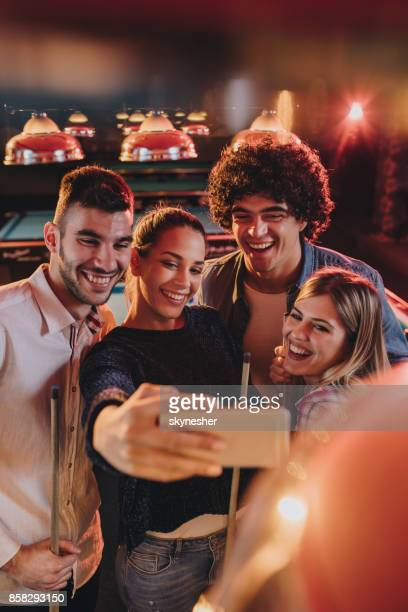 group of happy friends taking a selfie with smart phone in a pool hall. - vertical imagens e fotografias de stock