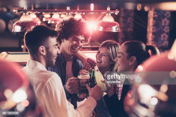 Grupo de amigos felices del tostado en una sala de billar.