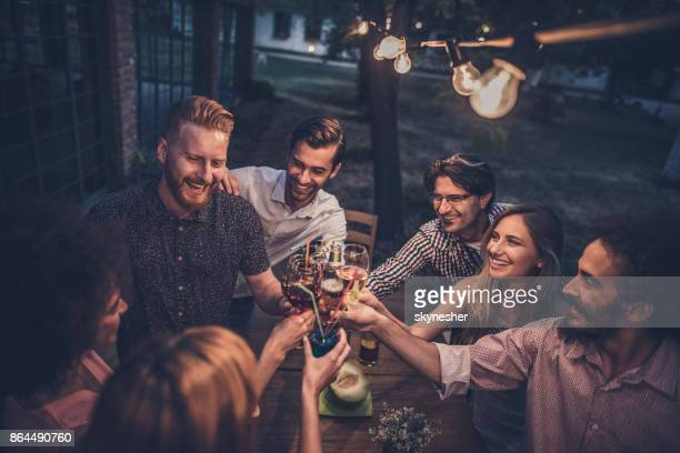 group of happy friends toasting on a night party in the back yard. - cocktail stock pictures, royalty-free photos & images