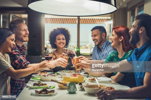 group of happy friends toasting while eating at dining table. - evening meal stock pictures, royalty-free photos & images