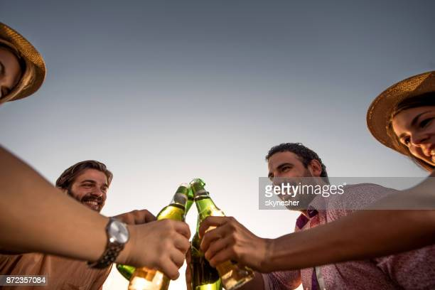 Group of happy friends toasting with beer against the sky.