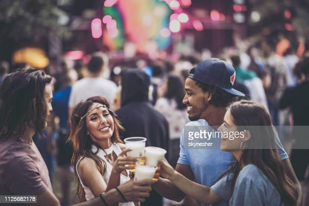 Group of happy friends toasting with beer on a music concert.