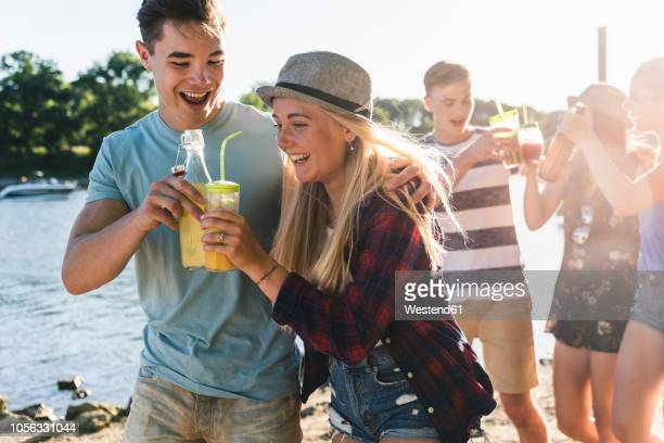 group of happy friends walking at the riverside toasting with drinks - kaltes getränk stock-fotos und bilder