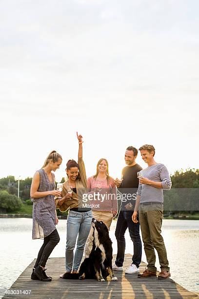 Group of happy friends with wineglasses enjoying on pier