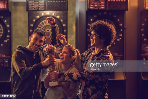 Group of happy friends with winning trophy celebrating victory in dartboard game.