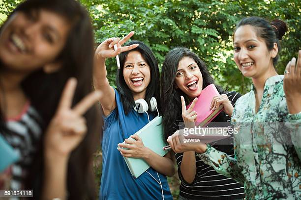 group of happy girl students showing peace hand sign. - girls stock pictures, royalty-free photos & images