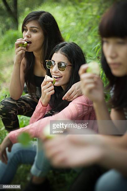 Group of happy girls eating fresh fruits in nature.