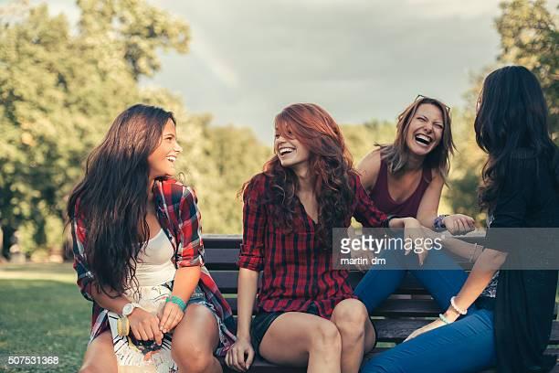 eine gruppe von glücklichen mädchen klatschen im park - sitzbank stock-fotos und bilder