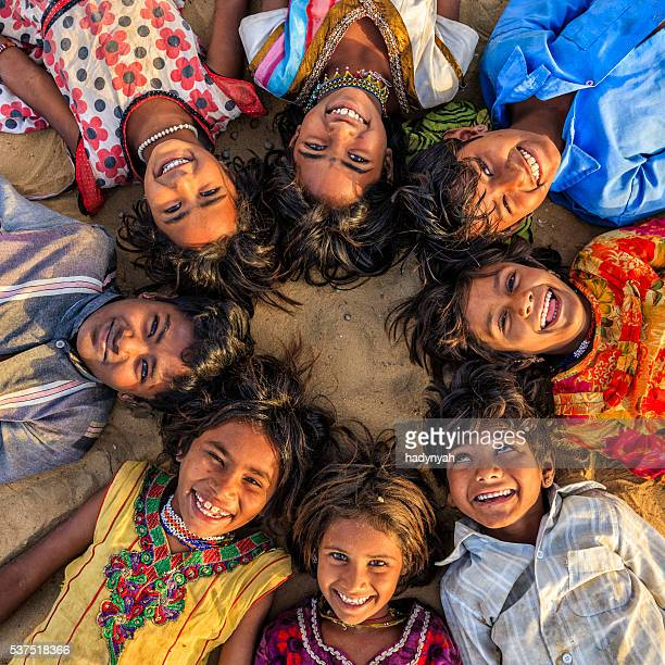 Group of happy Gypsy Indian children lying in circle, India