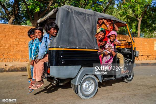 group of happy gypsy indian children riding tuk-tuk, india - rickshaw stock photos and pictures