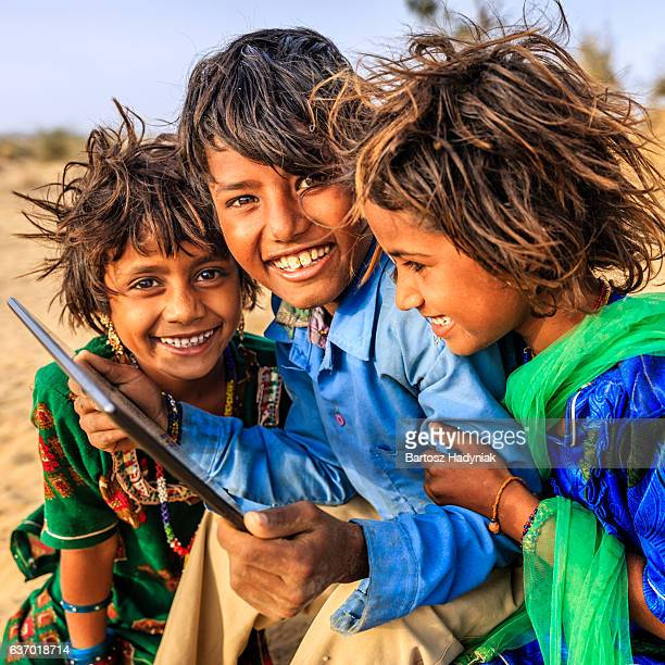 Group of happy Gypsy Indian children using digital tablet, India