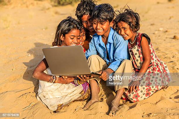 Group of happy Gypsy Indian children using laptop, India