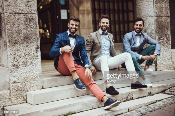 Group of happy hipsters sitting on staircase