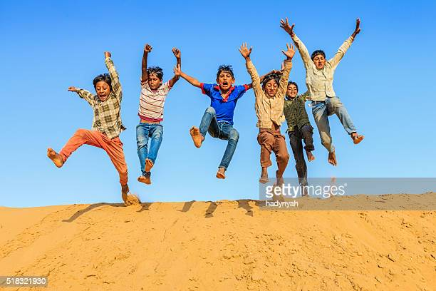 Group of happy Indian boys jumping off dune into sand