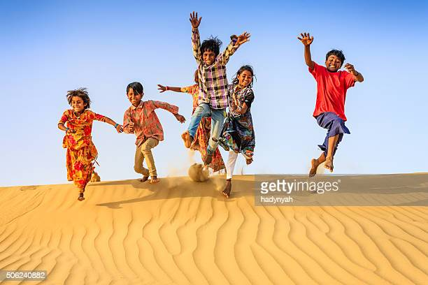 Group of happy Indian children jumping off dune into sand