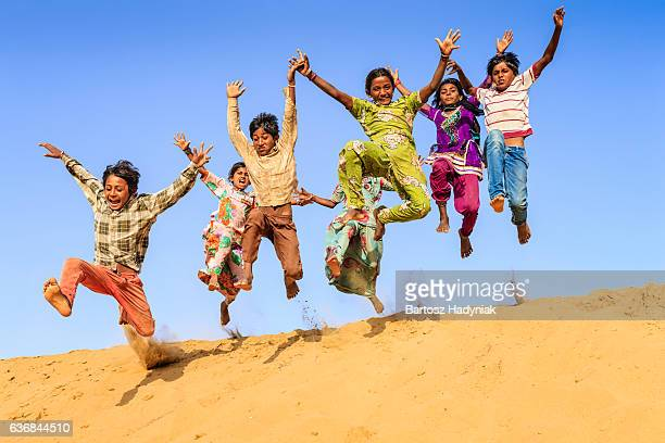 group of happy indian children jumping off dune into sand - play off stock pictures, royalty-free photos & images