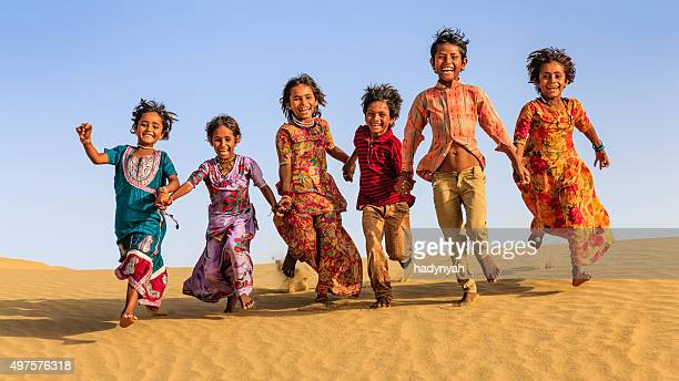 Group of happy Indian children running across sand dune, India