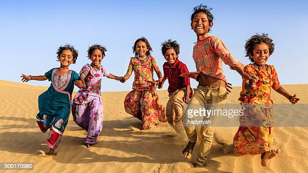 group of happy indian niños corriendo por duna de arena, india - cultura hindú fotografías e imágenes de stock