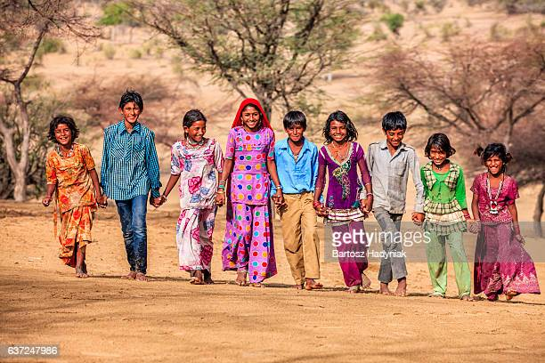 Group of happy Indian children walking across sand dunes, India