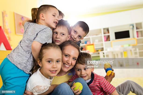 Eine Gruppe von glückliche Kinder umarmen Ihre Kinder Lehrer.