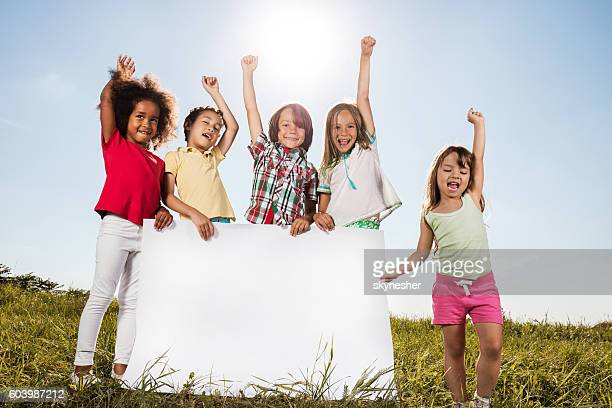 Group of happy kids holding big white banner in nature.