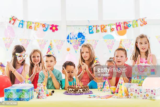 Group of happy kids singing and celebrating birthday.