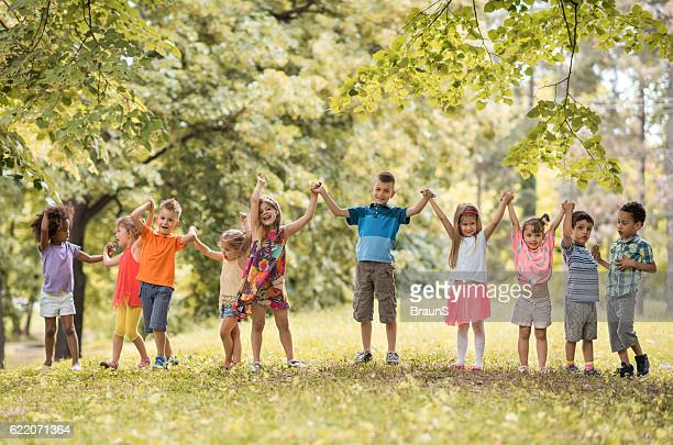 Group of happy little friends holding hands in the park.