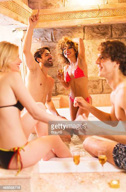 Group of happy people dancing and having fun in hot tub.
