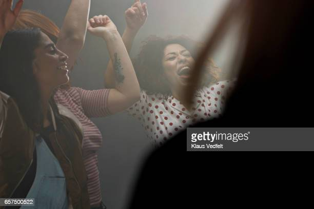 Group of happy people dancing in room with backlight